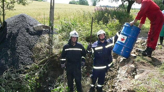 Hladinu potoka čistí dobrovolní hasiči z Nové Bystřice  Ladislav Kravar (vlevo) a Aleš Kubánek.