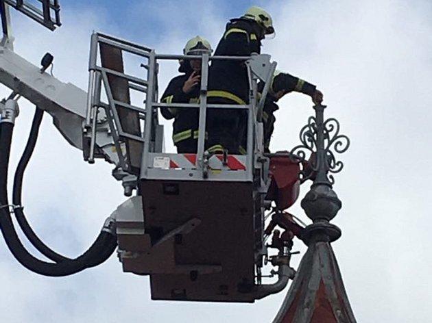 Hasiči ve Velenicích spravovali ulomenou ozdobu na střešní věžičce. Foto: Karel Jankuliak
