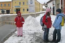 Dokunžacké školy dojíždí řada dětí z okolních vesnic, na snímku čekají na autobusové zastávce na náměstí v Kunžaku.