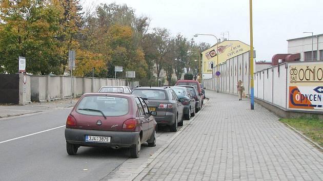 Pohled z kruhového objezdu do Vídeňské ulice na zaparkovaná auta.