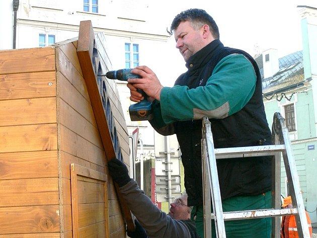 Pracovníci služeb města Jan Mach a František Hornyk (v pozadí) demontují stánek na jindřichohradeckém náměstí Míru.