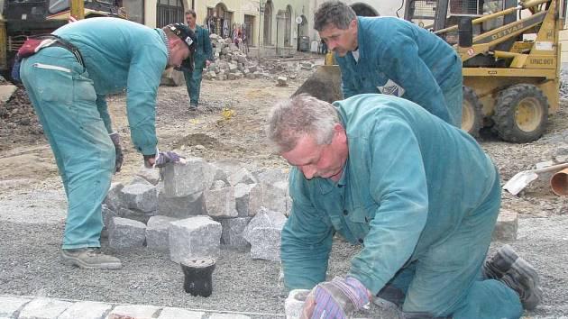 Pracovníci Jan Bielčik (v popředí), Josef Mikula a Michal Gärtner dláždí Žižkovo náměstí.