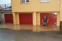 Přívalová voda při pondělní bouřce v Písečném zaplavila garáž.