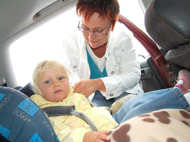 Pevné upoutání dítěte do sedačky a sedačky k sedadlu auta bezpečnostním pásem je základ k minimalizování zranění dítěte při případné autonehodě. Na snímku poutá do dětské autosedačky svou dceru Nelu Kateřina Svobodová.