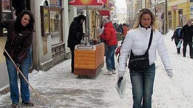 ÚKLID ULIC. Se sněhem bojovali včera také obchodníci v Panské ulici v Jindřichově Hradci, kteří nestíhali zametat prostor před obchody.