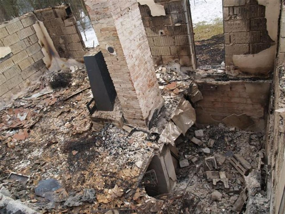 Pohled na plameny zcela zničenou chatu u Děbolína, kde policisté našli podezřelého hledaného muže.