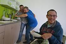 """Člověk by snad ani nevěřil, že je mytí nádobí taková legrace. Na snímku fyzioterapeuta Michala Vaculíka  """"objímá"""" Andrej Jaško. V popředí se směje Pavel Řeháček."""