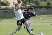 Fotbalisté Pelhřimova (v bílém Daniel Krtek) dokázali v derby Vysočiny jednoznačně porazit Vrchovinu (v tmavém Lukáš Wolker), které ve středu nasázeli pět gólů.