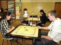 Carrom je hra pro dva či čtyři hráče. Podobá se kulečníku a hraje se na dřevěné desce.
