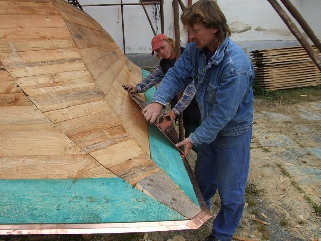 Řemeslníci v těchto dnech pokrývají opravený dřevěný krov měděným plechem.
