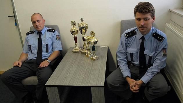 """Poháry si kameničtí policisté vysloužili za své sportovní úspěchy. """"Pro nás však není důležité vyhrát, ale zúčastnit se,"""" shodují se David Švéda (vlevo) a Radek Čekal."""