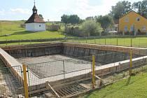 Drátěný plot kolem nádrže nahradí venkovský dřevěný. V pozadí opravená kaplička, vlevo zasazená lípa.