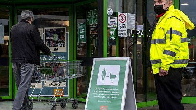 Popis fotky: Hypermarket v Ústí nad Labem - Pracovník ostrahy hlídá 18. listopadu 2020 před vstupem do hypermarketu v Ústí nad Labem. Od téhož dne platí pro provoz obchodů nová pravidla. Každý zákazník musí mít pro sebe při nákupu plochu 15 metrů čtverečn