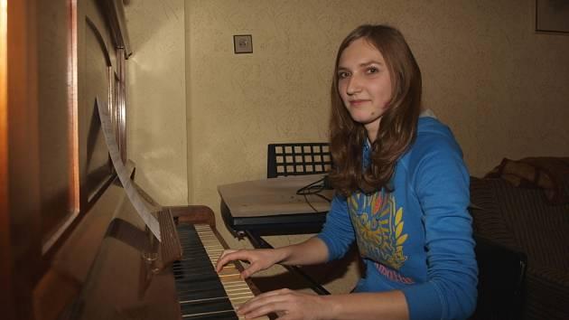 """Učí se skladby na klavíru. """"V kostele je zima a je to daleko, až přes silnici, takže raději zkouším doma,"""" směje se Eva Vlková."""