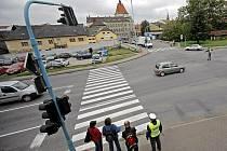 Policista míří do středu křižovatky a kolegyně vyčkává chodce, aby je informovala o správném postupu
