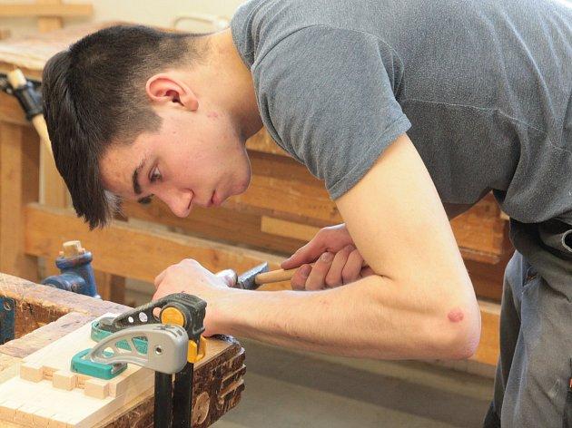 Mladí truhláři při soustředěné práci na soutěžním výrobku.