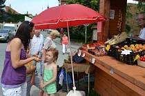 Stánky s ovocem a zeleninou lákají zákazníky.