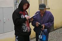 Typický obrázek ze středy: starší osoba zřejmě hledá na papírku napsané číslo svého mobilu.