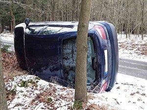 Havarované osobní auto skončilo na boku.