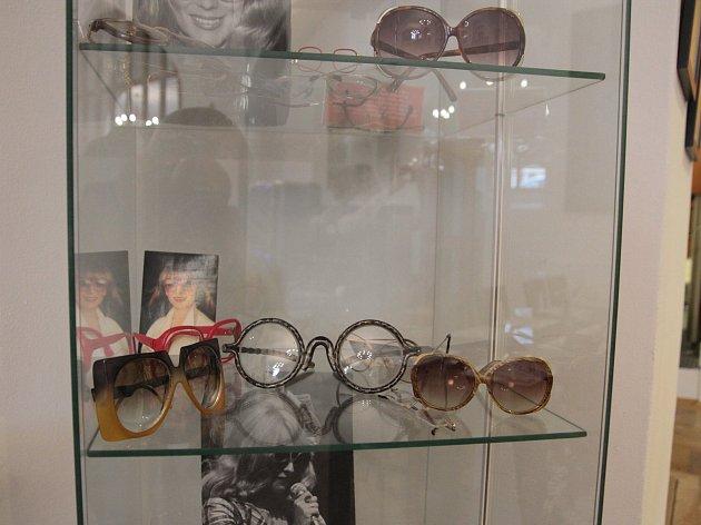 Brýle ve vitríně doplňují fotografie Nadi Urbánkové.