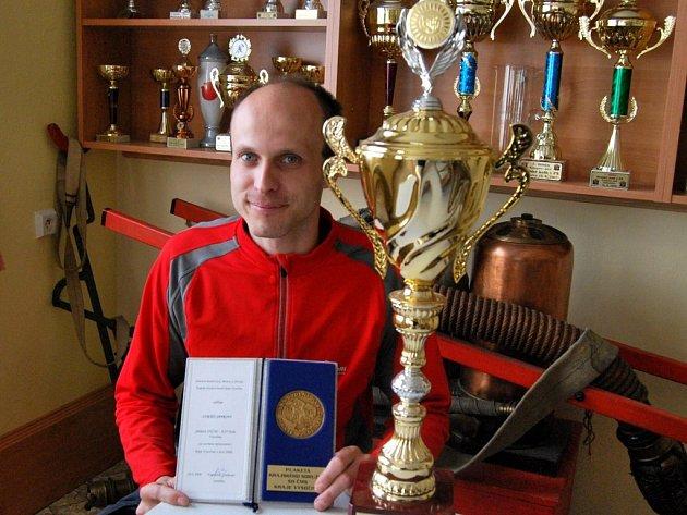 Lukáš Janko s medailí za prvenství v běhu na sto metrů překážek a pohárem počáteckého hasičské sboru.
