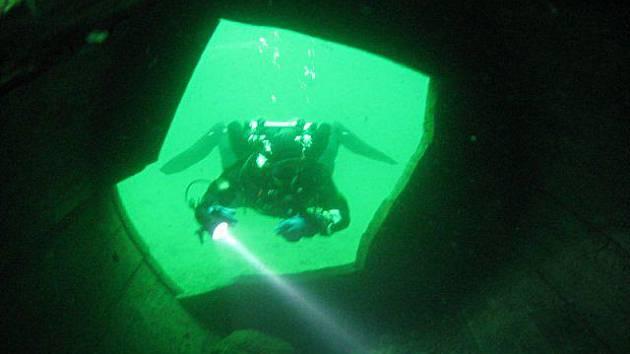 Potápěč prozkoumává jednu z atrakcí, která se nachází na dně zatopeného lomu v Horní Cerekvi. Po zatopení na počátku osmdesátých let tam zůstalo několik strojů.