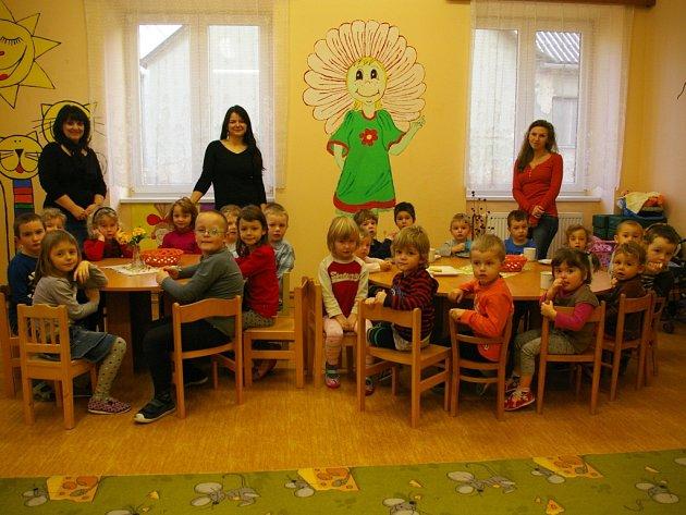 Na snímku jsou dvě skupiny dětí, učitelky Šárka Havránková (vpravo)a Jana Nevoralová (uprostřed) a ředitelka Pavlína Krátká (vlevo). V kuchyni pracuje Marie Makovičková.