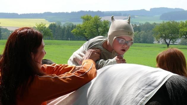 Děti si na koňský hřbet zvyknou.