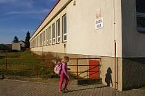 Před školou je hřiště, za ní směrem do polí by měla vyrůst nová mateřská škola.