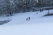 Kolem tribuny fotbalového stadionu v Žirovnici se děti klouzají.