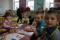 Část dětí u stolu tvoří z modelíny, jiné si hrají na koberci. V pozadí ředitelka Jana Leligdonová.
