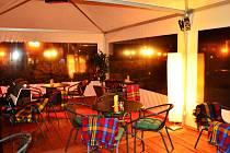 Přestože venku pomalu přituhuje, interiér kavárenského stanu působí vlídně i díky osvětlení a dekám.