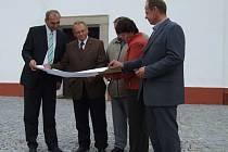 Zástupci městyse a pozvaní hosté v čele s politikem Janem Kasalem prohlížejí plán rekonstrukce náměstí Sv. Václava. Opravy centra městyse si vyžádaly čtyřmilionovou částku.