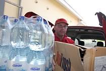 Zaměstnanec supermarketu Lubomír Mokrý ukládá darované potraviny do přistavené charitní dodávky.