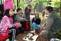 Děti právě poznávají šišky z různých stromů, vpravo je zkouší jeden z lesníků Městské správy lesů Pelhřimov.