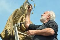Sochař Ivan Tlášek při opravě sochy.