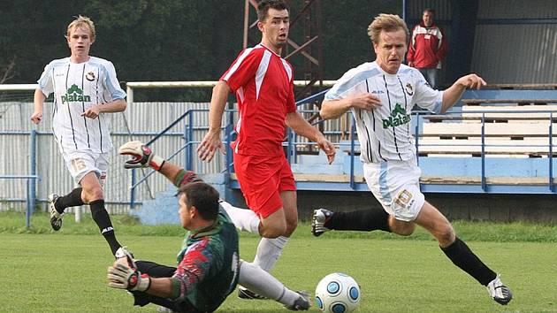 Miroslav Říha (vpravo) obchází brankáře hostí Davida Hejnu a střílí svůj třetí gól v zápase krajské I. A třídy Protivín - Netolice (4:0). V závěru střetnutí přidal Říha i čtvrtou trefu.
