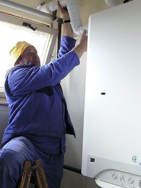 Plynofikace školy. Miloslav Těhle instaluje komín k již zapojenému plynovému kotli. Plynaři nyní pokračují v připojení těsně sousedící školní jídelny.