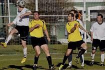 Domácí Miroslav Jaroušek odvrací hlavou míč do bezpečí před hostujícími hráči Kunešem a Fleischmannem v zápase krajského fotbalového přeboru, ve kterém Čížová hrála se Čkyní 0:0.