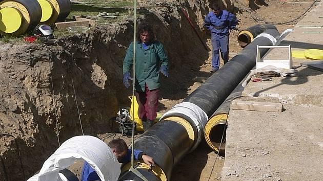 Na snímku ukládají pracovníci písecké teplárny potrubí do země.