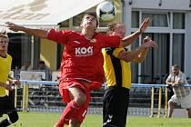Domácí David Chytrý (v červeném) v hlavičkovém souboji s Kiesslingem v zápase krajského fotbalového přeboru, ve kterém béčko Písku zvítězilo nad nováčkem z Dačic vysoko 8:3.