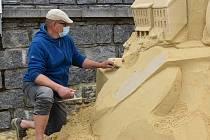 Sochaři pracují na pískových sochách u Otavy.