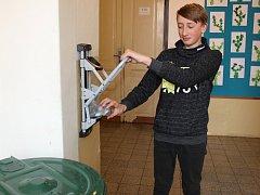 Žák 8. třídy ZŠ Mirovice Lukáš Mařík lisuje plastovou lahev.