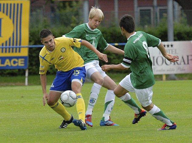 Domácí Karel Krejčí (ve žlutém) uniká Bedřichu Štumfalovi a Štěpánu Kozákovi ve středečním zápase III. fotbalové ligy, ve kterém Písek zvítězil nad Vltavínem 3:2.