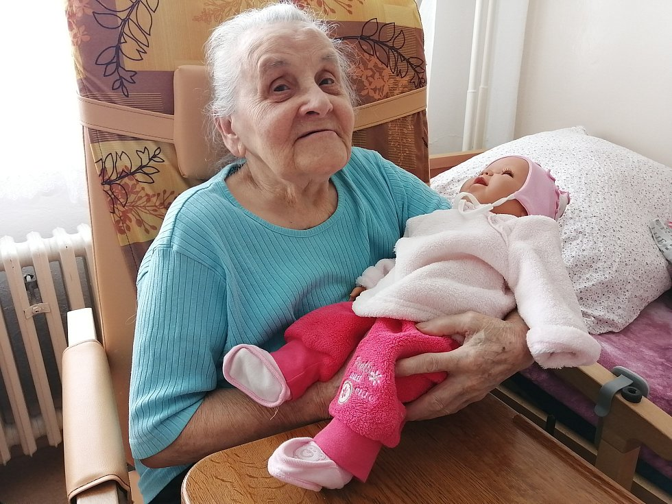 Klientka Alzheimercentra s terapeutickou panenkou.