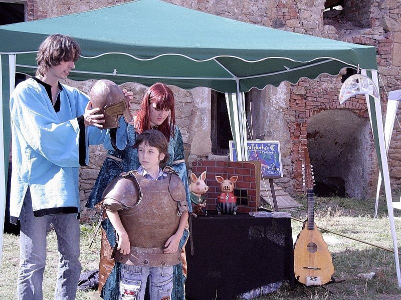 Jeden z   malých diváků Martin Trejla si za asitence  členů společnosti Jana Mikulce a Lenky Karabášové  vyzkoušel středověké brnění.