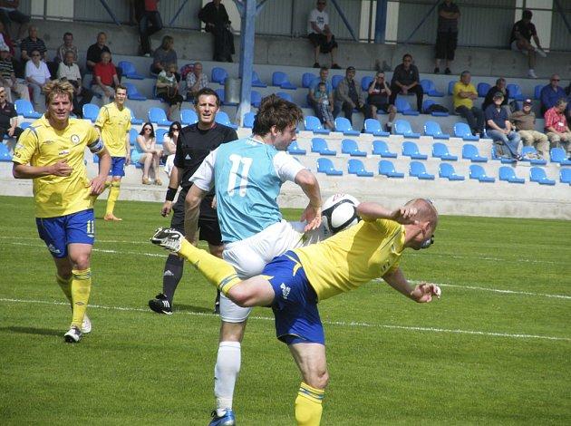 Domácí Michal Held (vpravo) bojuje v akrobatické pozici o míč s Danielem Zelenkou, vlevo všemu přihlíží kapitán domácího týmu Jan Zušťák. V sobotním utkání III. ligy prohráli fotbalisté Písku s Loko Vltavín 0:1.