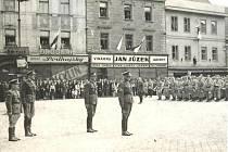 Fotografie zachycuje severní část Velkého náměstí  v Písku těsně před  vstupem do Heydukovy ulice. Snímek byl pořízen při slavnostní vojenské přehlídce po osvobození města v květnu 1945. Tehdy ještě vedle lahůdkářství Jan Jůzek byla drogerie Podhajský.