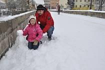"""Písek zaplavil další příval sněhu. Na Kamenném mostě si v sobotu alespoň malého sněhuláka """"ukouleli"""" Jiří Voráček s dcerou Bárou."""