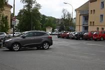 Křižovatka u náměstí, kde parkuje mnoho řidičů.